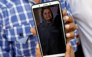 Shahid Ahmed, 45, holds his mobile phone displaying photo of his mother Irshad Begum, 72, who was killed in a plane crash, outside a morgue in Karachi, Pakistan May 23, 2020. REUTERS