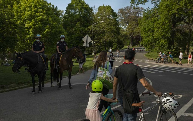 A family walks through New York's Prospect Park, May 16, 2020. Since April, doctors in New York State have been trying to understand a mysterious new syndrome affecting children that is linked to the coronavirus. The New York Times