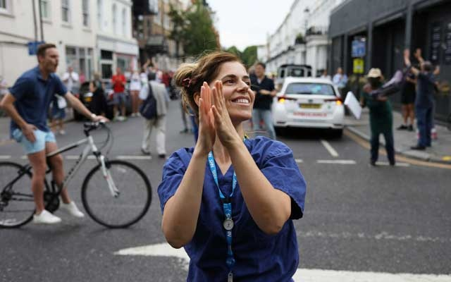 Members of the public and NHS workers react at the Chelsea and Westminster Hospital during the Clap for our Carers campaign in support of the NHS, following the outbreak of the coronavirus disease (COVID-19), London, Britain, May 21, 2020. REUTERS