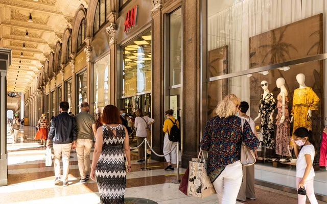 People wait in line to enter stores in Milan, May 21, 2020. Italy accounts for more than 40 percent of the world's luxury goods production, according to the consulting firm McKinsey. (Marta Giaccone/The New York Times)