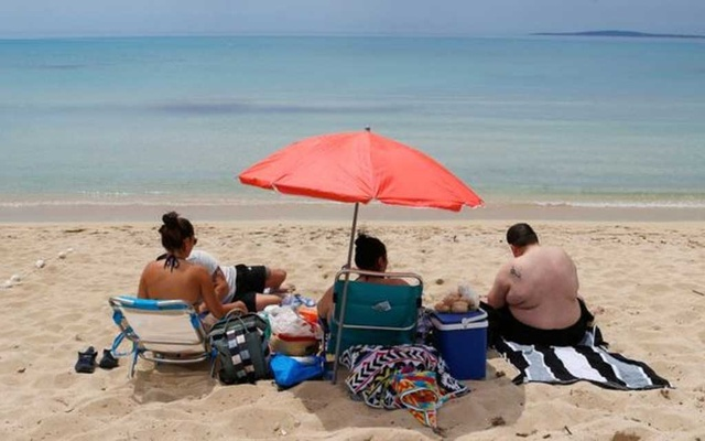 People sunbathe in El Arenal beach as some Spanish provinces are allowed to ease lockdown restrictions during phase two, amid the coronavirus disease (COVID-19) outbreak, in Mallorca, Spain, May 25, 2020. REUTERS