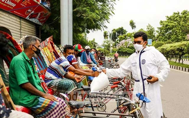 The traffic policemen of Dhaka's Tejgaon Industrial Area distributed a portion of their ration among rickshaw-pullers as Eid-ul-Fitr gift at Hatirjheel on Sunday. Photo: Mahmud Zaman Ovi