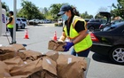 City workers hand out meals to school parents in Santa Clara, Calif, on April 23, 2020. The New York Times