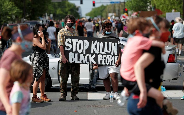 Protesters gather at the scene where George Floyd, an unarmed black man, was pinned down by a police officer kneeling on his neck before later dying in hospital in Minneapolis, Minnesota, US, May 26, 2020. REUTERS