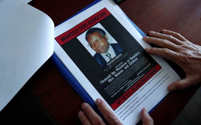 Eric Emeraux, head of the Gendarmerie's Central Office for Combating Crimes Against Humanity, Genocides and War Crimes (OCLCH), displays documents with a wanted poster depicting a photograph of Felicien Kabuga during an interview with Reuters at his office, about the arrest of Rwandan genocide fugitive suspect Felicien Kabuga, in Paris, France, May 19, 2020. REUTERS