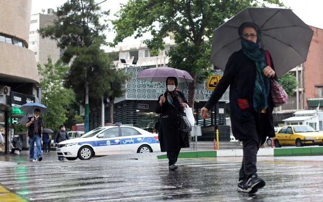 Iranians wear protective face masks, following the outbreak of the coronavirus disease (COVID-19), as they walk in Vali-E-Asr street, in Tehran, Iran, May 20, 2020. REUTERS