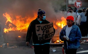 A man wearing a face mask holds a sign near a burning vehicle at the parking lot of a Target store during protests after a white police officer was caught on a bystander's video pressing his knee into the neck of African-American man George Floyd, who later died at a hospital, in Minneapolis, Minnesota, US, May 28, 2020. REUTERS