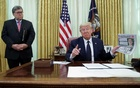 US President Donald Trump speaks to reporters about an executive order regarding social media companies as Attorney General Bill Barr listens in the Oval Office of the White House in Washington, US, May 28, 2020. Reuters