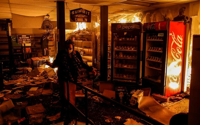 A woman reacts while protesters set fire in a liquor store as demonstrations continue after a white police officer was caught on a bystander's video pressing his knee into the neck of African-American man George Floyd, who later died at a hospital, in Minneapolis, Minnesota, US, May 28, 2020. REUTERS/Carlos Barria