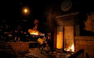 A protester sets fire to the entrance of a police station as demonstrations continue after a white police officer was caught on a bystander's video pressing his knee into the neck of African-American man George Floyd, who later died at a hospital, in Minneapolis, Minnesota, US, May 28, 2020. REUTERS/Carlos Barria