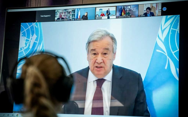 FILE PHOTO: United Nations Secretary-General Antonio Guterres is seen on a video screen during a virtual climate summit in Berlin on April 28, 2020. Michael Kappeler/Pool via REUTERS