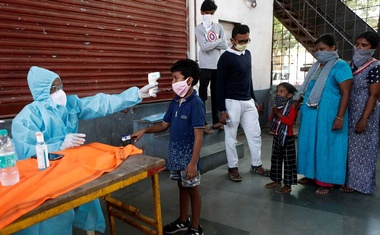 A healthcare worker checks a boy's temperature with an infrared thermometer at a camp in Dharavi, one of Asia's largest slums, during an extended lockdown to slow the spread of the coronavirus disease (COVID-19), India, May 29, 2020. Reuters