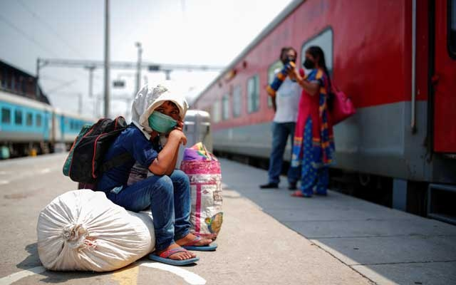 A child sits on luggage at a platform as he waits to board a train at a railway station after a few restrictions were lifted during an extended nationwide lockdown to slow the spread of the coronavirus disease (COVID-19), in New Delhi, India, June 1, 2020. REUTERS