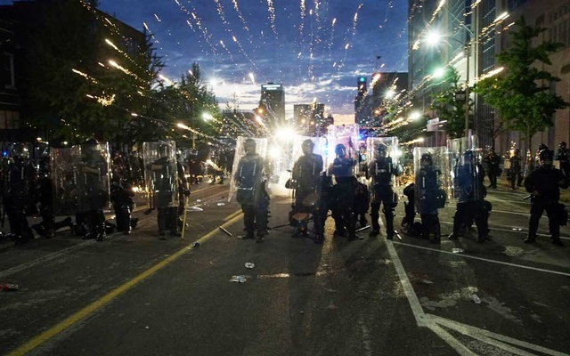 Fireworks explode behind police officers during a protest against the death in Minneapolis police custody of African-American man George Floyd, in St Louis, Missouri, US, June 1, 2020. Reuters