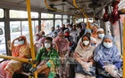 Government employees sit next to each other on a bus despite orders to maintain physical distancing during travel. Photo: Asif Mahmud Ove