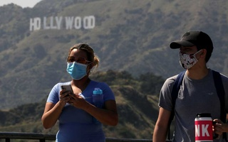 People wearing face masks walk past the Hollywood sign in the distance, after a partial reopening of Los Angeles hiking trails during the outbreak of the coronavirus disease (COVID-19) at Griffith Park in Los Angeles, California, US, May 9, 2020. REUTERS