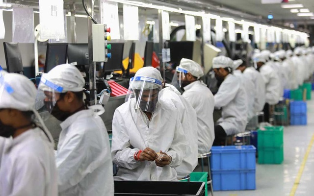 Workers wearing face shields work at an assembly line of mobile phones at Lava International Limited's manufacturing plant, after some restrictions were lifted during an extended nationwide lockdown to slow the spread of the coronavirus disease (COVID-19) in Noida, India, May 12, 2020. Reuters