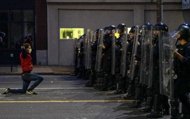 A man gets on his knees in front of police officers during a protest against the death in Minneapolis police custody of African-American man George Floyd, in St Louis, Missouri, US, June 1, 2020. REUTERS