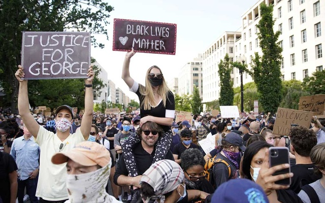 Demonstrator hold signs during a protest against the death in Minneapolis police custody of George Floyd, in Washington, DC, US, June 2, 2020. REUTERS