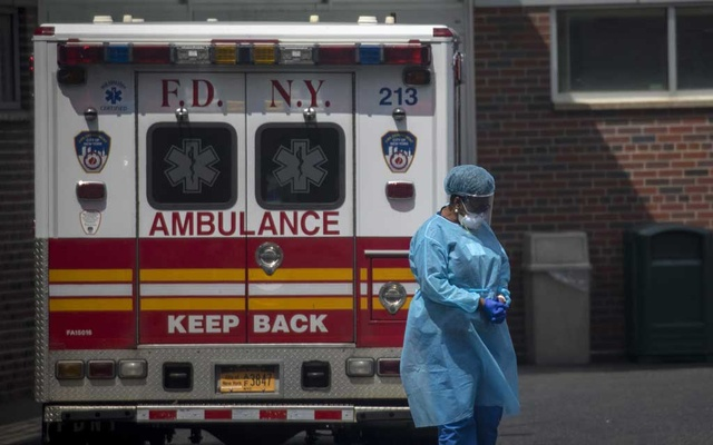 FILE -- A hospital worker pauses next to an ambulance outside of Kingsbrook Jewish Medical Center in Brooklyn, May 11, 2020. Despite promising early results and the Trump administration's strong interest in nurturing a government-industry partnership, substantial hurdles remain, and many scientists consider President Donald Trump's goal of having a vaccine widely available by early next year to be optimistic, if not unrealistic. (Dave Sanders for The New York Times)