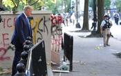 US President Donald Trump walks past a building defaced with graffiti by protestors in Lafayette Park across from the White House after walking to St John's Church for a photo opportunity during ongoing protests over racial inequality in the wake of the death of George Floyd while in Minneapolis police custody, outside the White House in Washington, US, Jun 1, 2020. REUTERS