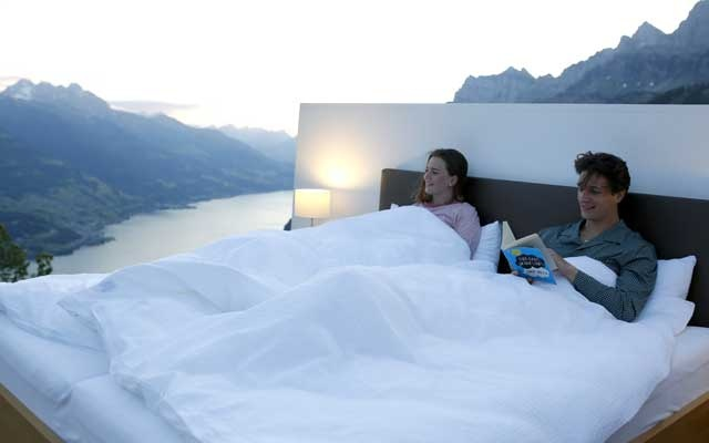 Dominic Gregorin and Anja Wachter (L) pose in the bedroom of the Zero-Real-Estate land art installation by Swiss artists Frank and Patrik Riklin, as the outbreak of the coronavirus disease (COVID-19) continues, on an alp in front of the Churfirsten mountain range and Lake Walen near Walenstadt, Switzerland May 29, 2020. REUTERS