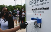 Maryland election judge Cassandra Campbell watches a voter places their ballot in a curbside ballot drop box to prevent the spread of the coronavirus disease during the Maryland US presidential primary election as other voters stand in a long line waiting to cast their votes in College Park, Maryland, on June 2. REUTERS