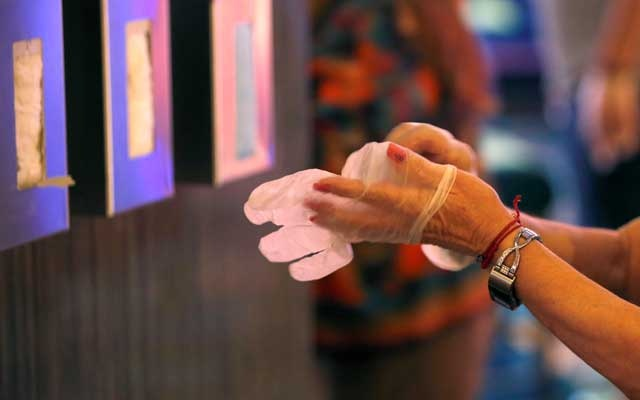A woman puts on protective gloves at a hand washing station on the casino floor during the reopening of Bellagio hotel-casino, closed since Mar 16, 2020 as part of steps to slow the spread of the coronavirus disease (COVID-19), in Las Vegas, Nevada, US, Jun 4, 2020. REUTERS