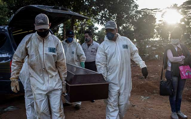 Grave diggers carry the coffin of a coronavirus victim before burial at the Vila Formosa cemetery in São Paulo, Brazil, May 28, 2020. As the West settles into a grinding battle with the virus, it surges across the Middle East, Africa, Latin America and South Asia. (Victor Moriyama/The New York Times)