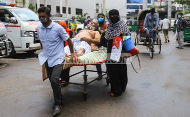 Relatives stretchering a patient to the COVID-19 unit of the Dhaka Medical College Hospital despite having no protective clothng as there was no health worker available. Photo: Asif Mahmud Ove