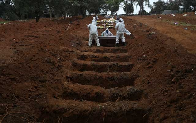 Gravediggers wearing protective suits bury the coffin of 48-years-old Jose Soares, who died from the coronavirus disease (COVID-19), at Sao Luiz cemetery, in Sao Paulo, Brazil, June 4, 2020. Reuters
