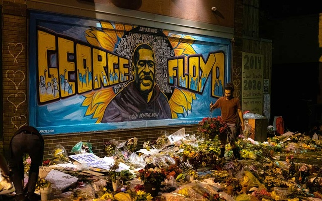 Volunteers help tidy the memorial for George Floyd, featuring a mural created by three artists, after a long day of rain showers, in Minneapolis, Minn, on June 2, 2020. The New York Times