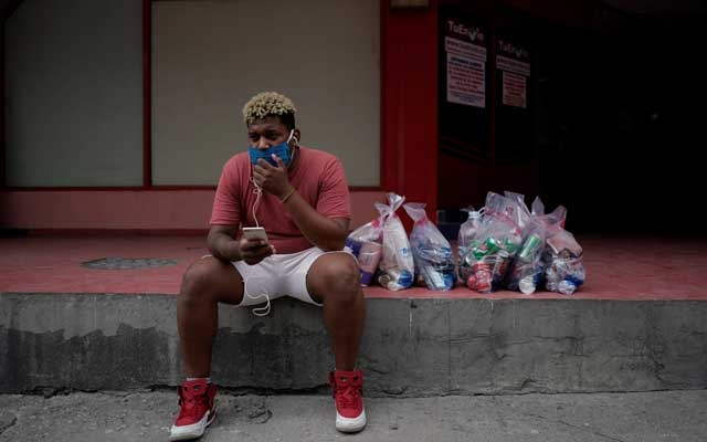 Singer Hector Leon, 30, speaks on his smartphone through the Internet after picking up products he bought online amid concerns about the spread of the coronavirus disease (COVID-19) outbreak, in downtown Havana, Cuba, May 25, 2020. REUTERS