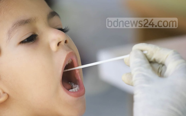 A child gives a sample for COVID-19 testing at a booth set up in Government Unani and Ayurvedic Medical College and Hospital in Dhaka's Mirpur. Photo: Asif Mahmud Ove