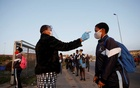 A learner is screened as schools begin to reopen after the coronavirus disease (COVID-19) lockdown in Langa township in Cape Town, South Africa, Jun 8, 2020. REUTERS/FILE