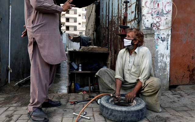 A labourer wearing protective face mask fills air in a tyre at a workshop along a road, as the outbreak of the coronavirus disease (COVID-19) continues, in Karachi, Pakistan, June 12, 2020. Reuters