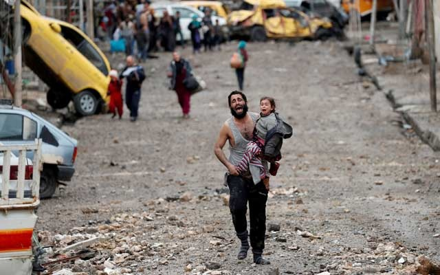 A man cries as he carries his daughter while walking from an Islamic State controlled part of Mosul. REUTERS