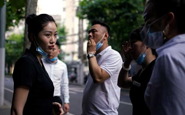 People wearing face masks stand on a street, following the coronavirus disease (COVID-19) outbreak, in Shanghai, China June 17, 2020. REUTERS