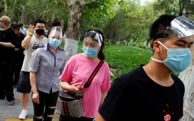 People wearing face masks and shields line up to get a nucleic acid test at a park in the Fengtai district, after a spike of cases of the coronavirus disease in Beijing on Jun 17. REUTERS
