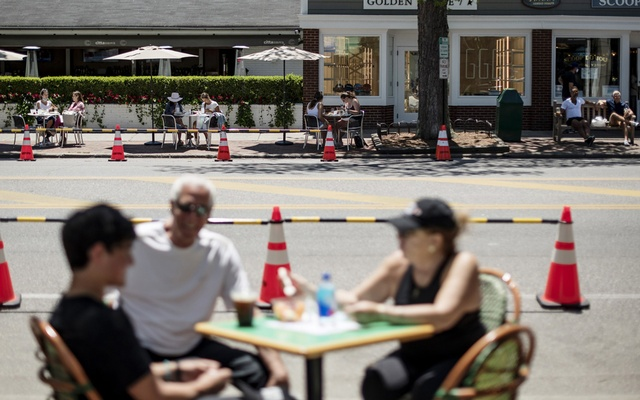 Diners sit at restaurant tables set up outdoors on both sides of Newton Lane in East Hampton, NY, Jun 13, 2020. To enhance social distancing and help curb spread of the coronavirus, cities are accelerating applications and waiving fees to allow al fresco dining, but the moves are disrupting neighborhoods and cutting much-needed tax revenue. The New York Times