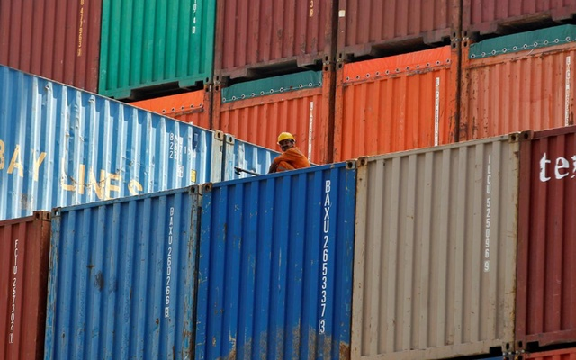 A worker sits on a ship carrying containers at Mundra Port in the western Indian state of Gujarat Apr 1, 2014. REUTERS