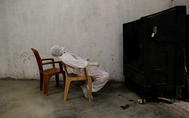 Renu, a medical health worker, relaxes in front of an air cooler at a school which was turned into a centre to conduct tests for the coronavirus disease (COVID-19), amidst the spread of the disease, in New Delhi, India Jun 19, 2020. REUTERS