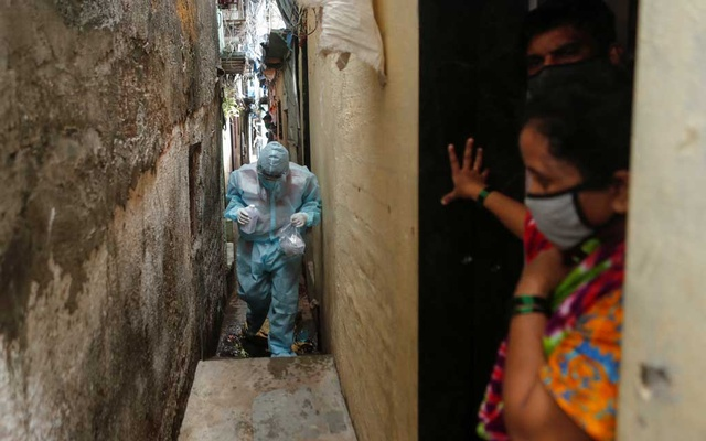 People stand at the entrance of their house as a healthcare worker wearing personal protective equipment (PPE) arrives to check the temperature of residents of a slum during a check-up camp for the coronavirus disease (COVID-19) in Mumbai, India Jun 17, 2020. REUTERS