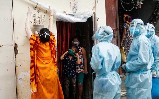 A woman rolls up a protective sheet at the entrance of a house so healthcare workers wearing personal protective equipment (PPE) can check the temperature of residents during a check-up camp for the coronavirus disease (COVID-19) in Mumbai, India Jun 17, 2020. REUTERS