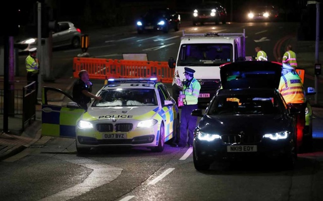 Police officers and their vehicles are seen at the scene of reported multiple stabbings in Reading, Britain, June 20, 2020. REUTERS