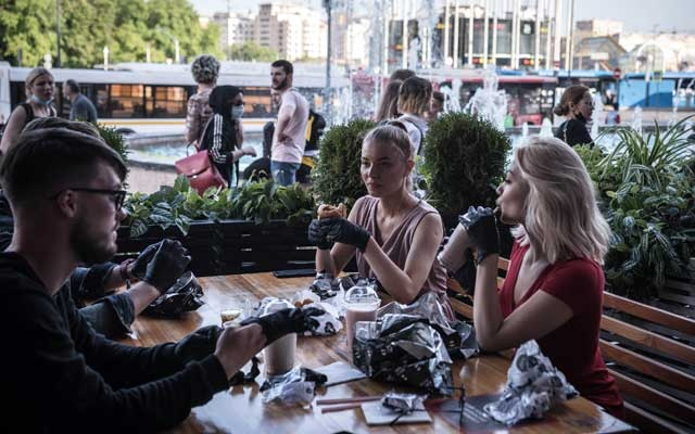 Customers wearing gloves eat burgers on the terrace of Black Star Burger in Moscow on June 16, 2020. Status-conscious fast-food joints across Eastern Europe have offered their diners disposable gloves for years and the idea may find a wider audience in the pandemic era. (Sergey Ponomarev/The New York Times)