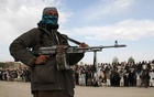 A member of the Taliban insurgent and other people stand at the site during the execution of three men in Ghazni Province April 18, 2015. REUTERS/Stringer
