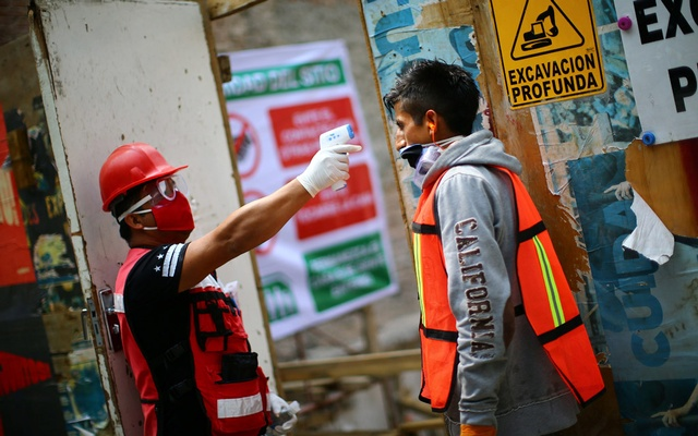 An employee, wearing a face mask, scans the temperature of a construction worker during the first day of the country's gradual re-opening of the economy for