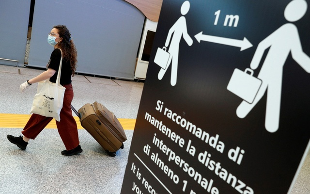 A passenger wearing a protective face mask passes near a sign indicating to keep the social distancing at Fiumicino Airport, where new security measures have been implemented ahead of a further loosening of movement restrictions on June 3, when Italy is due to reopen its borders to travellers from Europe to unwind its rigid lockdown due to the coronavirus disease (COVID-19), in Rome, Italy, May 28, 2020. REUTERS/Guglielmo Mangiapane