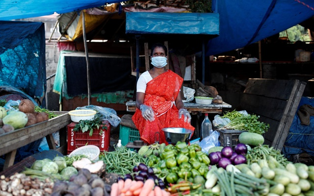 A woman wearing a protective face mask and gloves waits for customers at her vegetable shop outside a slum area, during an extended nationwide lockdown to slow the spreading of the coronavirus disease (COVID-19), in New Delhi, India, June 24, 2020. REUTERS